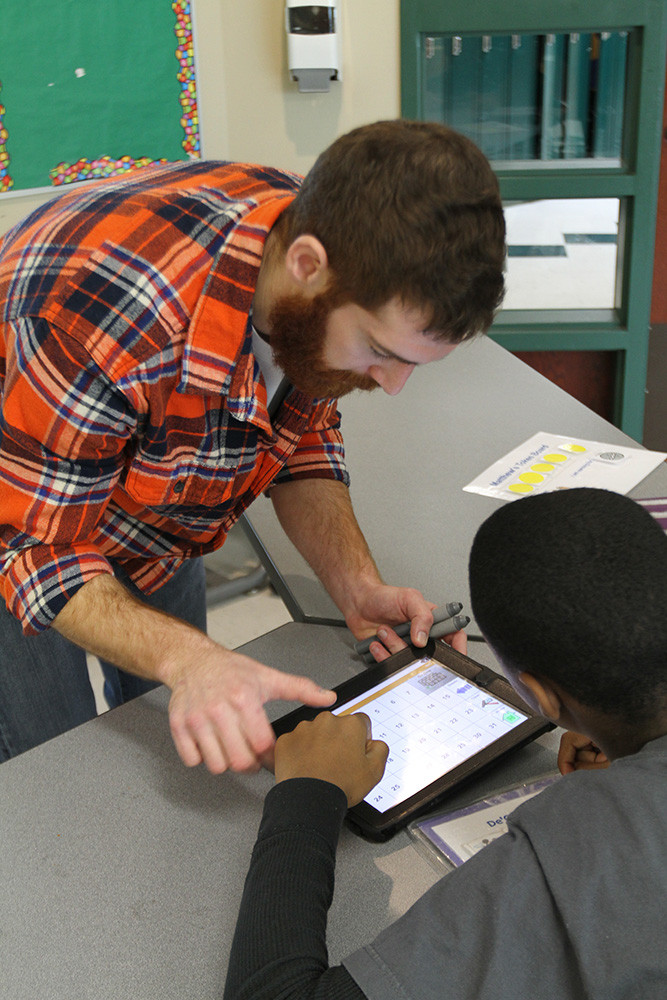 Teacher helping student with iPad.