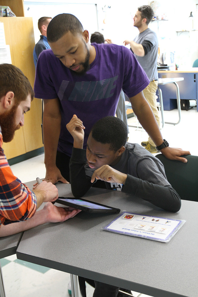 Teachers working with student on iPad.