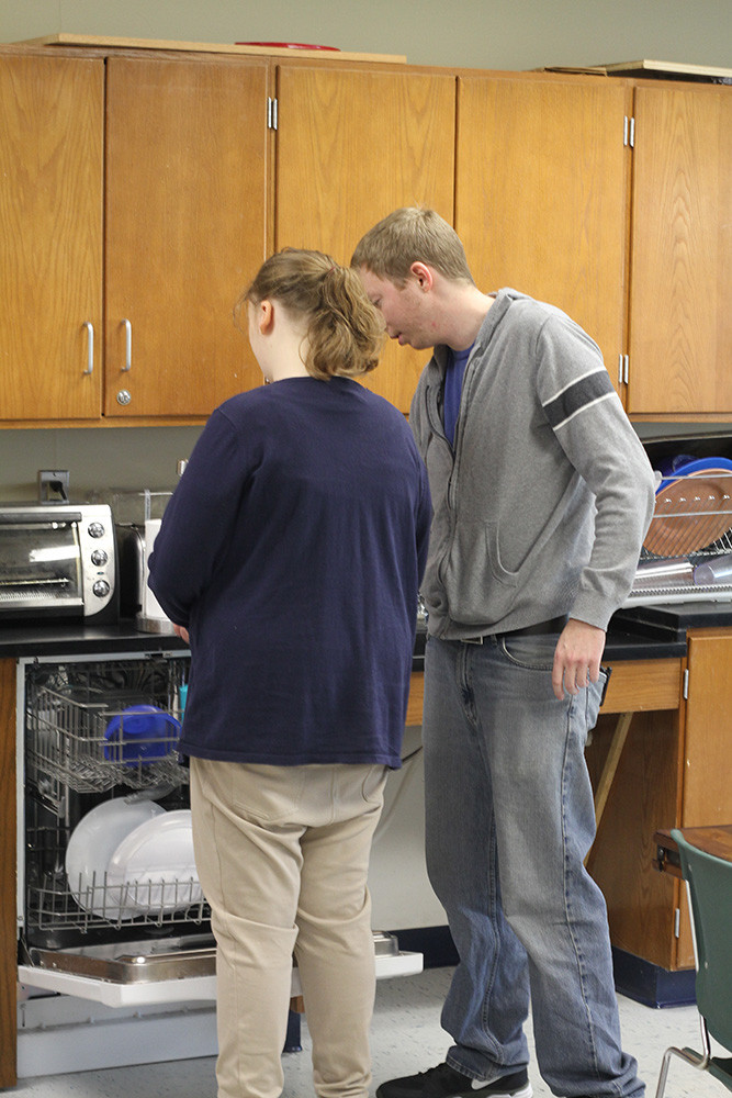 Teacher and student practicing life skills in kitchen setting.
