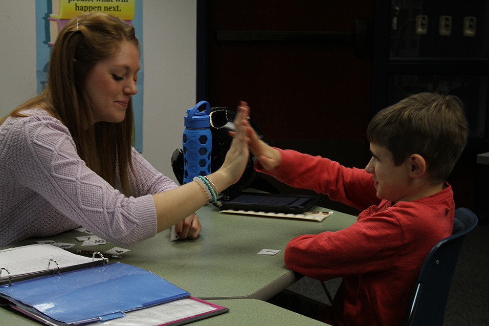 Teacher giving student a high-five.